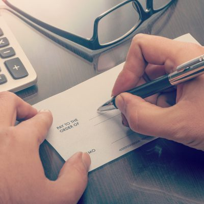 Man writing a payment cheque at the table with calculator and glasses